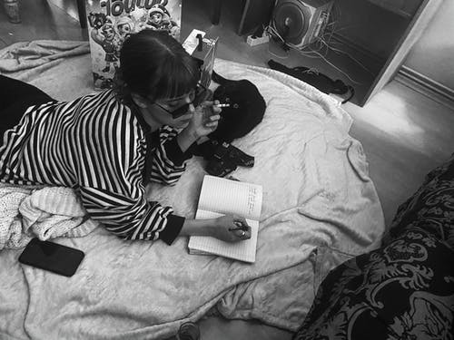 Stylish woman smoking while writing in notebook on bed