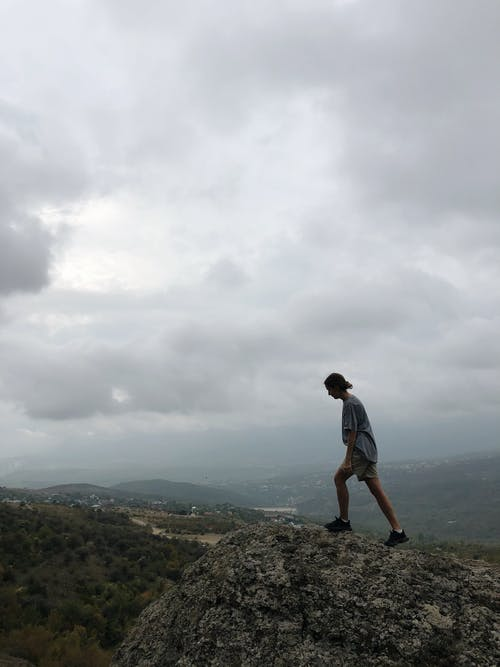 Unrecognizable traveler walking on rocky cliff in highland area against misty sky