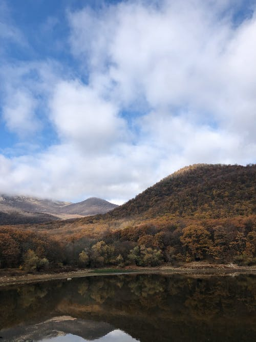 Breathtaking scenery of calm lake surrounded by mountains covered with lush golden trees against cloudy blue sky on autumn day
