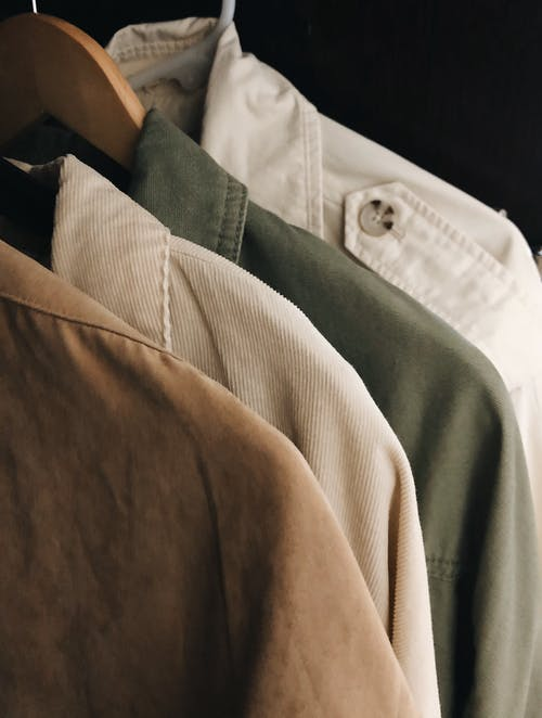 High angle collection of various stylish casual shirts hanging on rack in wardrobe against black background