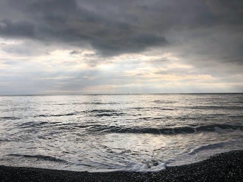 Peaceful scenery of waving foamy endless ocean washing stony coast against dramatic sunset sky