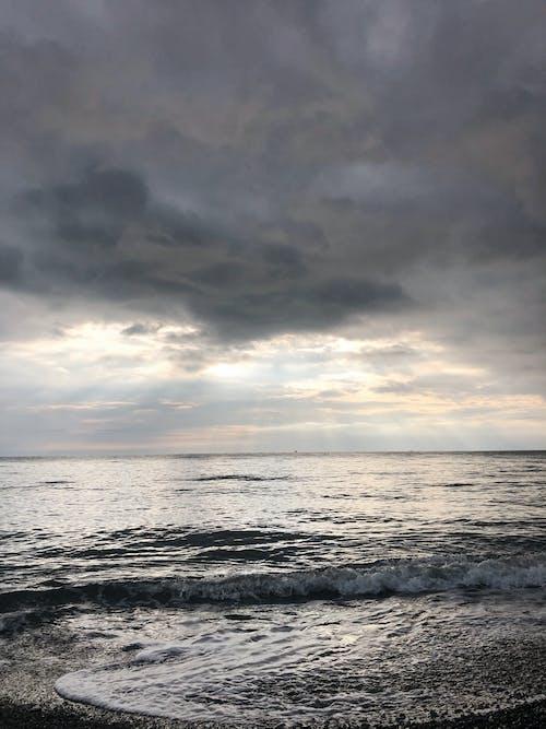 Stormy sea with foamy waves against cloudy sundown sky