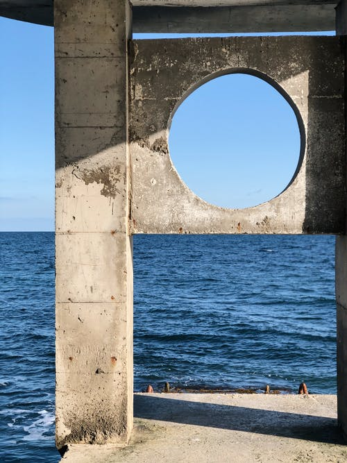 Weathered aged concrete pier with columns and hole near waving sea against cloudless blue sky on sunny day