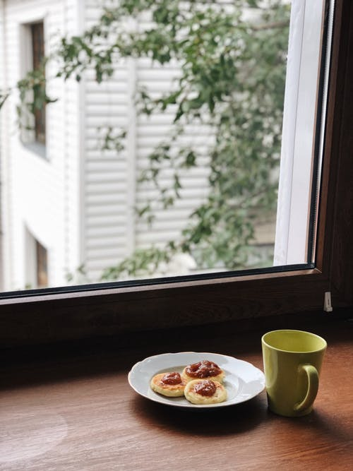 Breakfast with sweet dessert and cup of coffee served on windowsill
