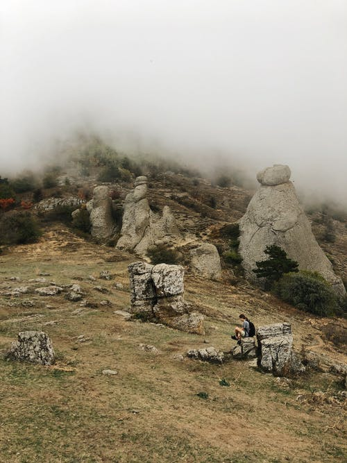 Side view of unrecognizable hiker relaxing on rough stone and admiring picturesque view of Valley of Ghosts with various rocky formations against foggy sky in Crimea