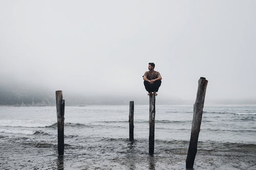 Serious male sitting on top of wooden pillar on coast with waving stormy sea against misty sky in overcast weather in nature