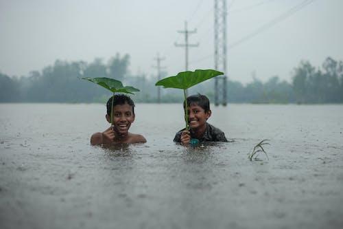 Happy ethnic boys in river under rain