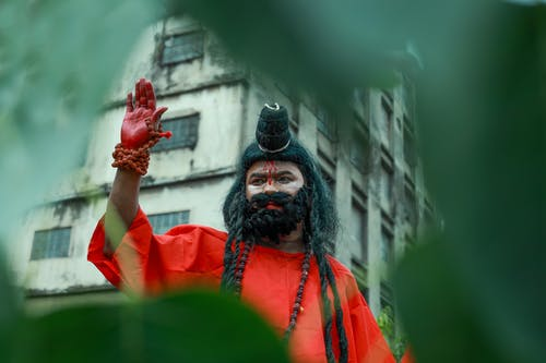 Low angle view of Indian male with painted face and dark hair wearing authentic outfit standing with red hand raised through blurred green hole
