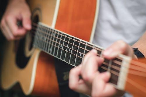 Guitarist pinching chord while playing acoustic guitar