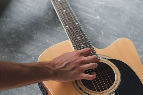 High angle of crop anonymous male guitarist touching acoustic guitar while practicing melody