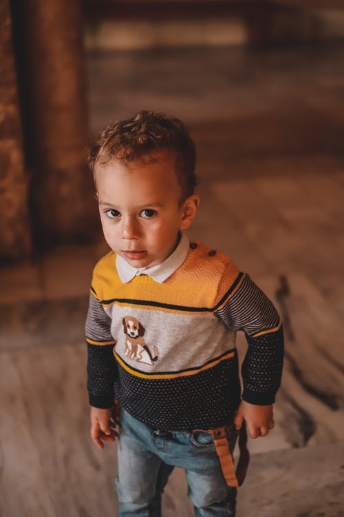 A Boy in Yellow and Black Sweater Looking at Camera