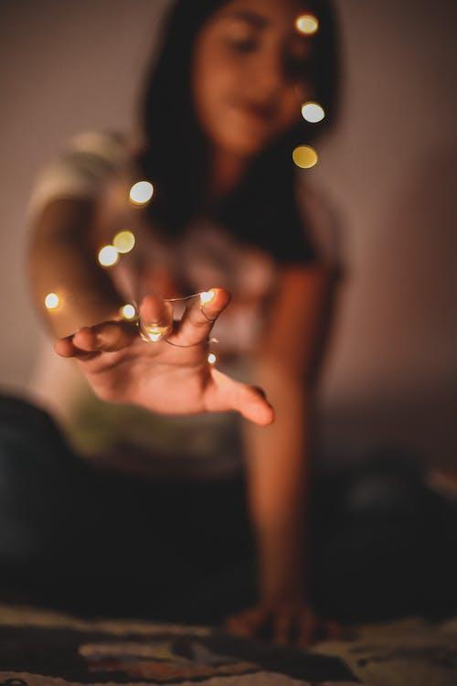 Woman in Black Shirt Holding String Lights