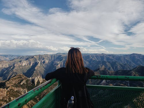 Woman in Black Jacket Standing on Top of a Mountain