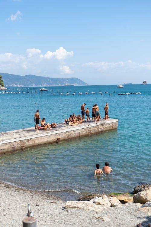 People Sitting on Concrete Dock