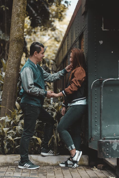 Full body side view of tender boyfriend touching cheek of girlfriend while standing near metal wagon and looking at each other in nature with tree