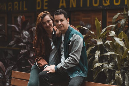Positive couple sitting on bench near green foliage