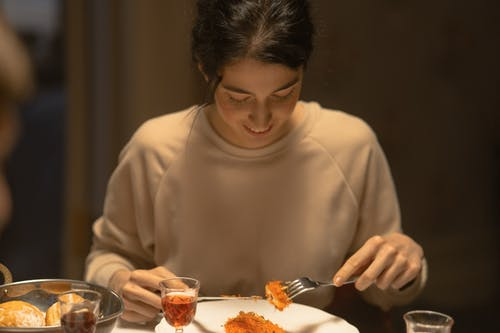 Young Woman Eating At The Table
