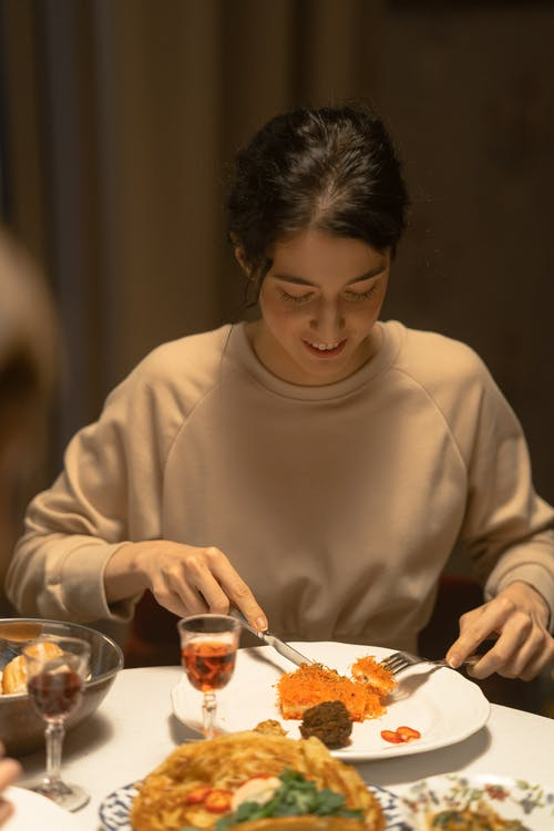 Woman in Beige Sweater Eating