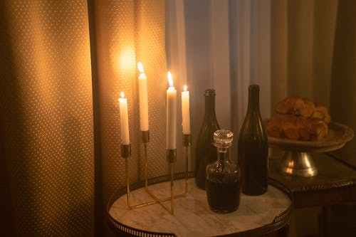 Lighted Candles And Wine Bottles on Wooden Table