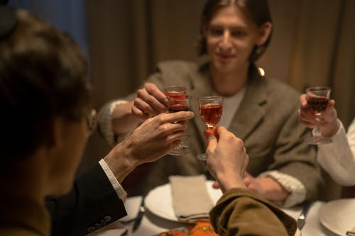 Group Of People Making A Toast With Red Wine