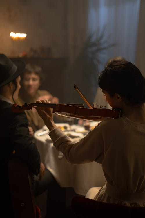 Woman Playing Violin At A Dinner Table During Hanukkah Celebration