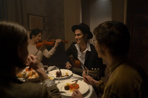 People Gathered At A Dinner Table While Playing Musical Instruments