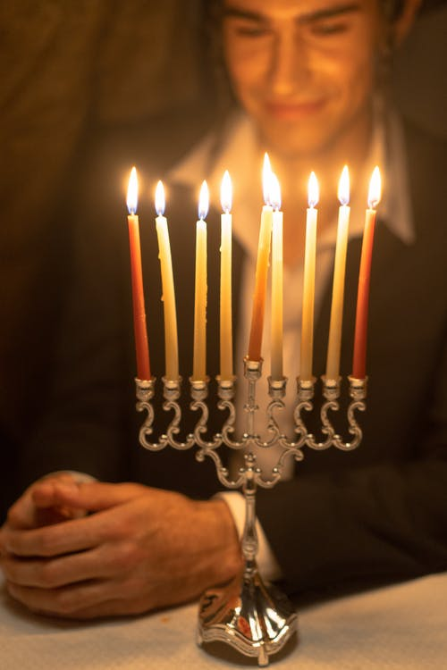 Man Looking At Lighted Candles Of A Candelabrum