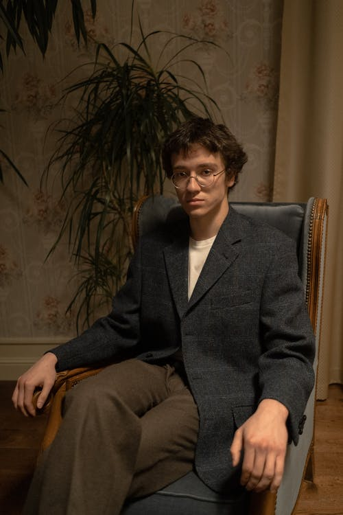 Man in Black Suit Jacket Sitting on Brown Wooden Armchair
