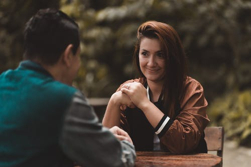 Positive woman at table with anonymous man in park