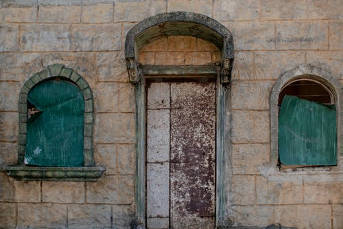 Facade of aged abandoned stone house with shabby wooden door and windows in old town
