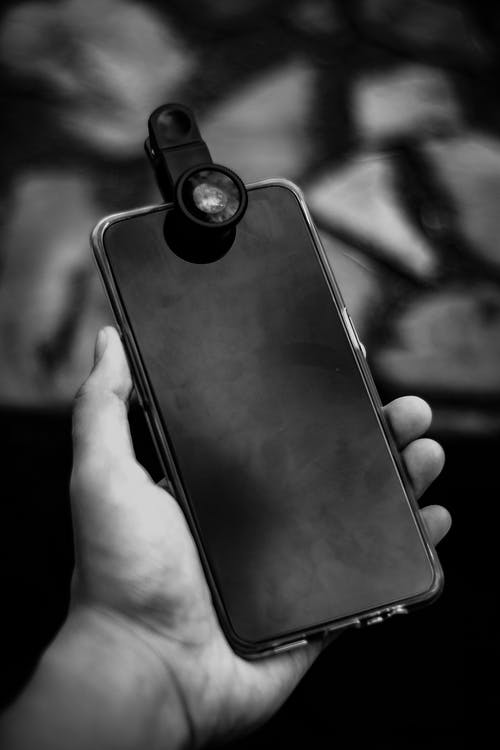 From above of black and white crop anonymous man showing mobile phone with attached optical lens