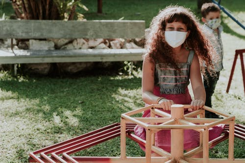 Positive girl in medical mask looking at camera while riding carousel and having fun on playground with little boy in park