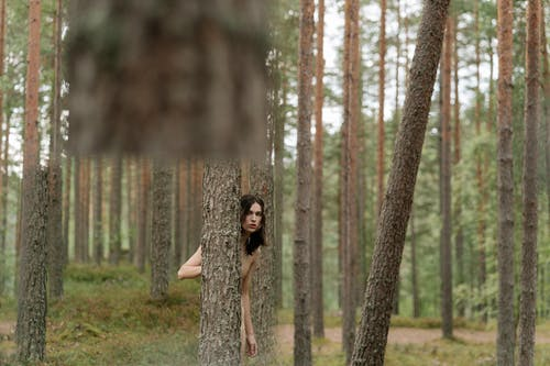 Woman in Black Sleeveless Dress Standing in the Woods