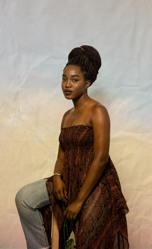 Calm African American female model wearing casual clothes with bare shoulders looking at camera while sitting on bright background during photo shoot