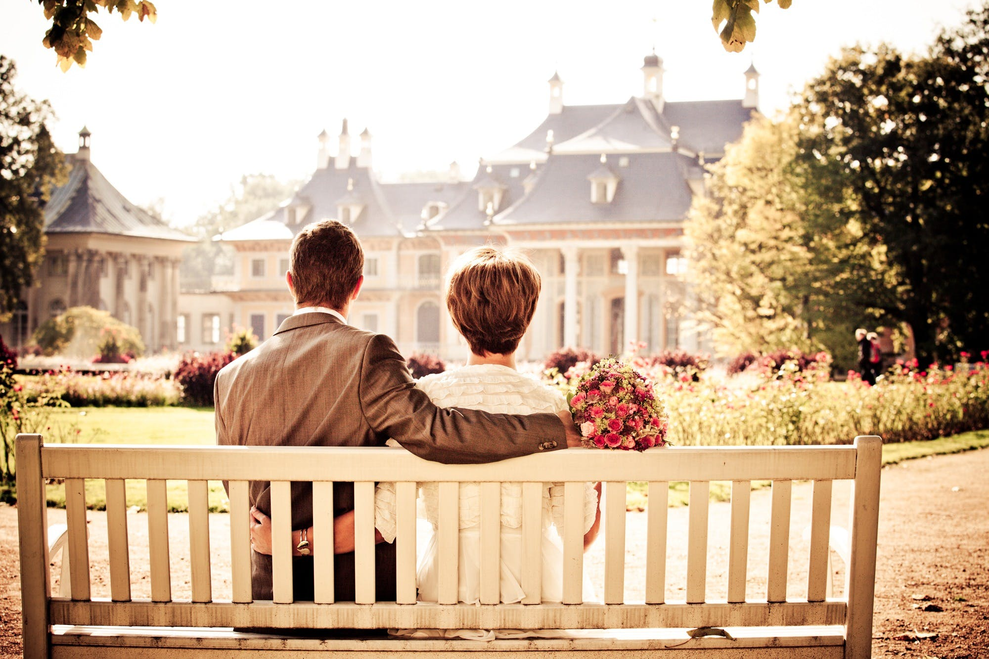 Couple Sitting on Wooden Bench While Watching White and Blue House