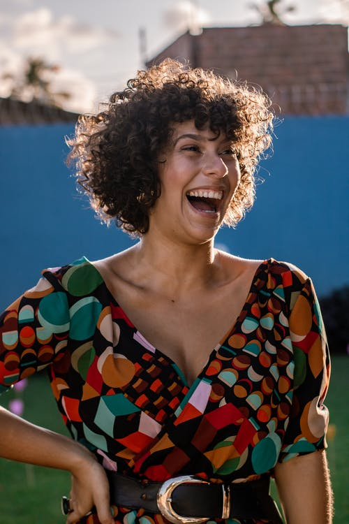 Laughing woman in trendy dress on street