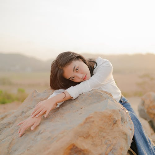 Woman in White Long Sleeve Shirt Lying on Brown Rock