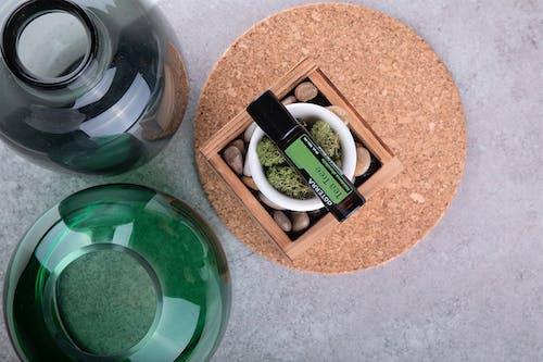 Green Glass Bottle Beside Brown Wooden Box
