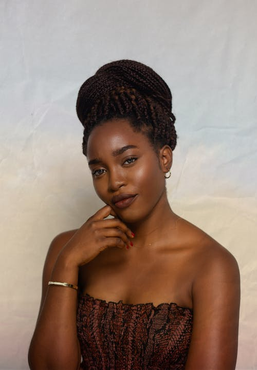Attractive African American female wearing accessories and casual clothes with bare shoulders on colorful background with hand at chin