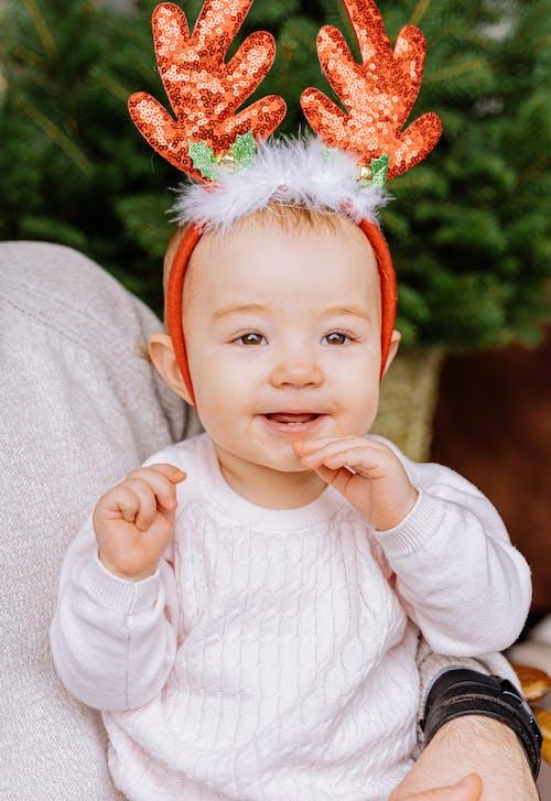 Baby in White Long Sleeve Shirt Wearing A Headdress