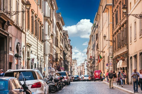 Narrow street with cars and motorcycles parked near historic buildings located in city in Europe and with people walking outside under blue sky in summer sunny day
