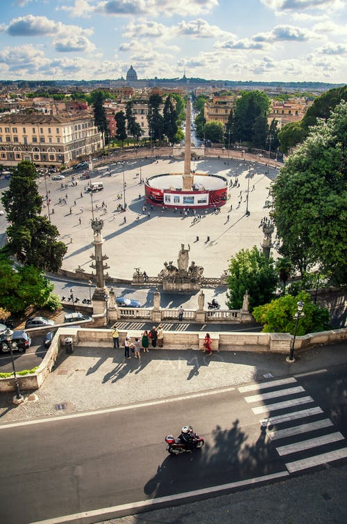 Famous historic landmark located in Rome in Italy and called Piazza del Popolo in sunny summer day under blue cloudy sky with buildings on background