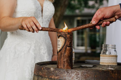 Crop newlyweds lighting candle during ceremony