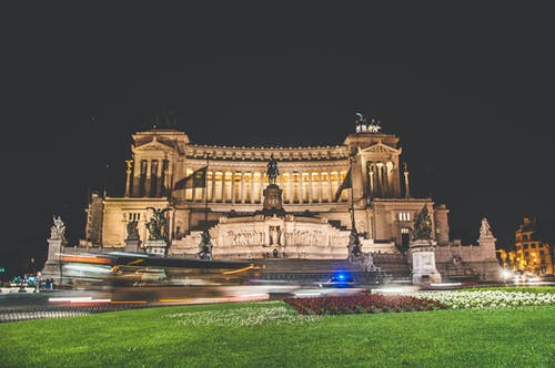 Exterior of Victor Emmanuel II National Monument or Vittoriano located in Rome in Italy at night with green grass and flowers nearby