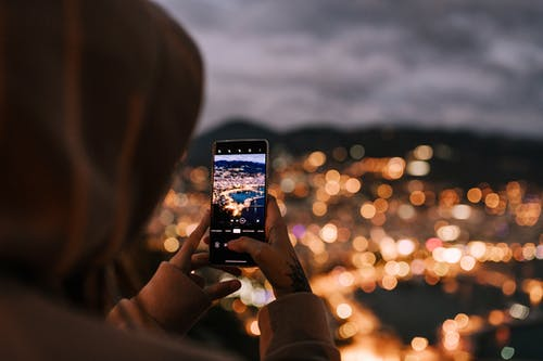 From behind crop person in hoodie taking picture on mobile phone of scenic night city located on hillside and illuminated by bright electric lights