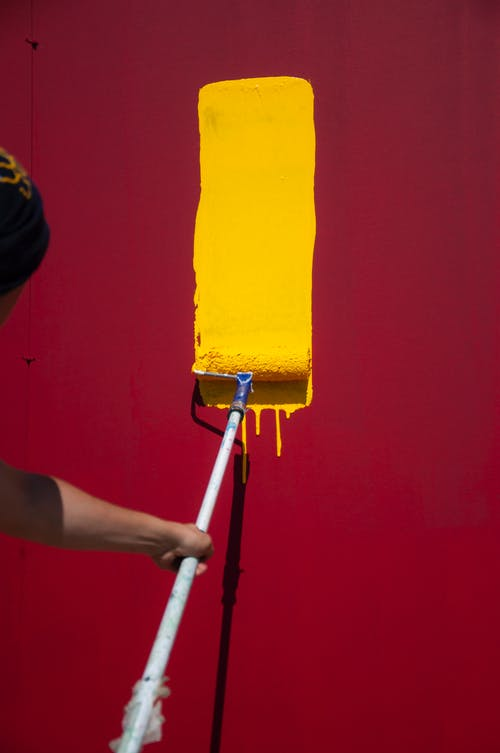 Anonymous painter with yellow roller painting