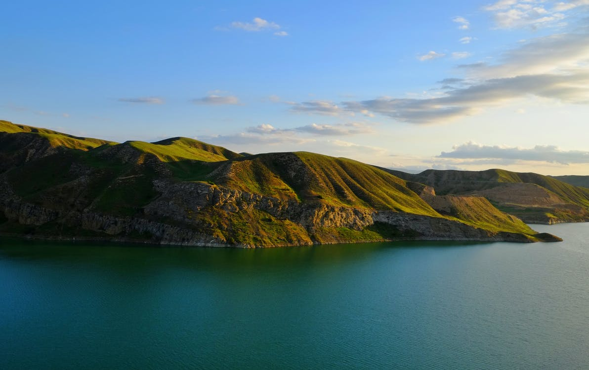 Green and Brown Mountains Beside Body of Water Under Blue Sky