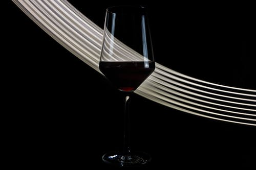 Wineglass of fragrant exquisite red wine placed against black background with white shiny lines
