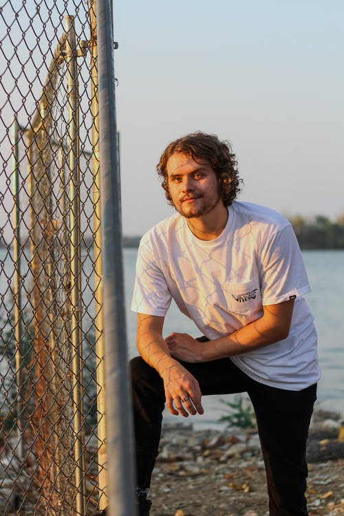 Man in White Crew Neck T-shirt and Black Pants Sitting on Gray Concrete Surface