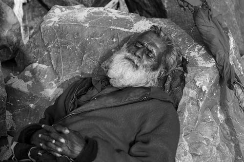 Grayscale Photo of Man Lying on Rock